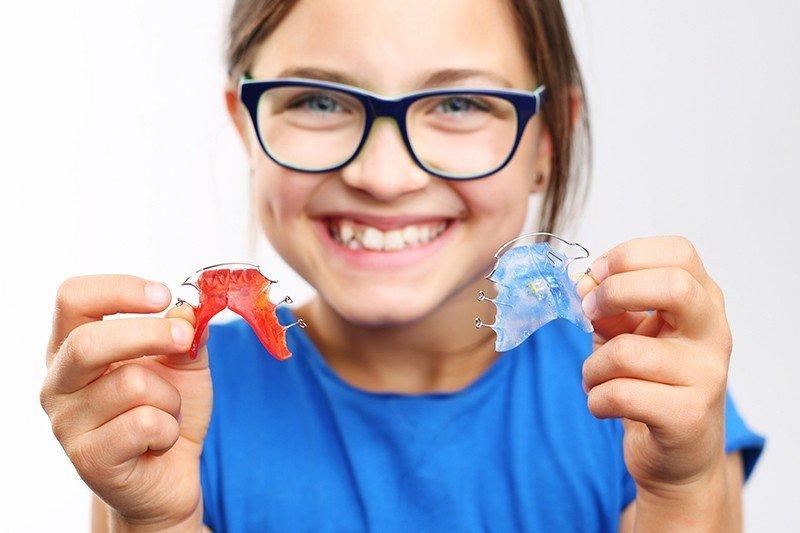 Dziecko zaparatem ortodontycznym wdłoniach